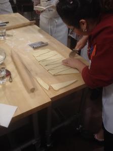 Kursledaren Nathalie skär upp formen till vanliga croissanter